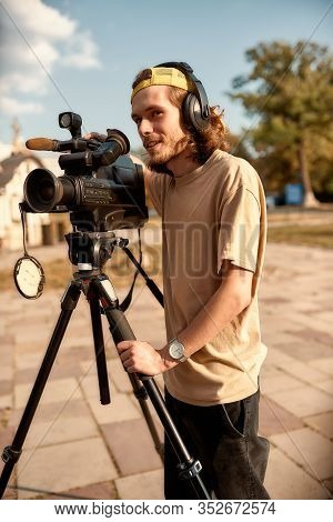 Full-length Portrait Of Young Professional Cameraman In Headphones, Recording A Video Footage Using