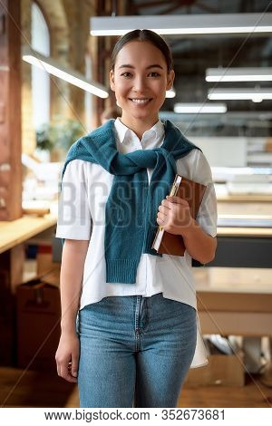 Portrait Of Attractive Ambitious Asian Businesswoman In Casual Wear Holding Notebook, While Smiling