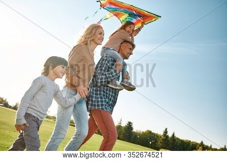 Portrait Of Cheerful Parents With Two Kids Walking With Kite In The Park On A Sunny Day. Family, Kid