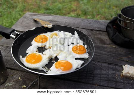 Fried Eggs Cooked In Frying Pan On Camping Gas Stove On Old Wooden Table. Outdoor Cooking At Forest.