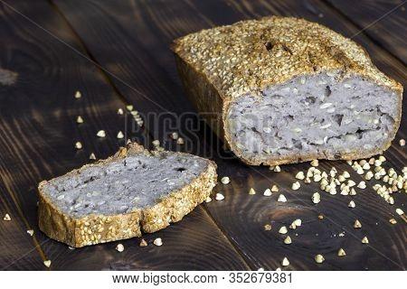 Vegan Buckwheat Bread. Freshly Baked Traditional Bread On Dark Brown Wooden Table. Scattered Grains