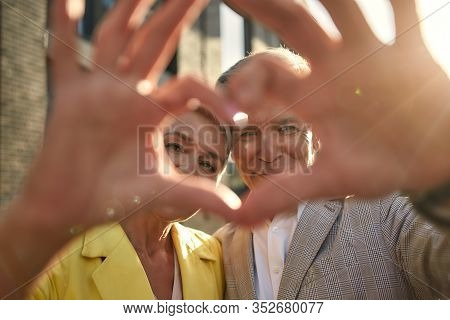 Always Together. Portrait Of Cute And Cheerful Senior Couple Making A Heart Shape With Their Hands A