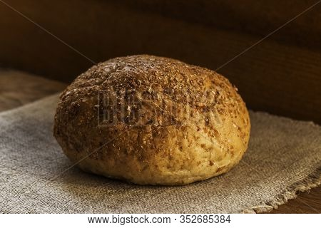 A Loaf Of Rye Bread Lies On A Natural Blue Textile Napkin, The Concept Of Healthy Food,
