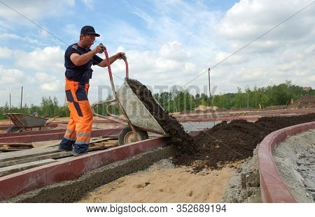 Moscow - August 2012: Workers in uniform are carrying out earthwork. Landscaping of new residential buildings.