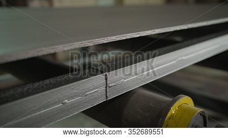Continuous Sheet Of Metallic Material Being Fed Through Machine. Metal Sheet On The Conveyor. Painti