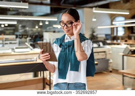 Portrait Of Attractive Ambitious Asian Businesswoman In Casual Wear And Glasses Looking At Tablet Pc