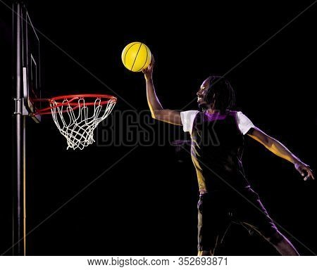 one mature african basketball player man in studio multiple exposure in studio isolated on black background