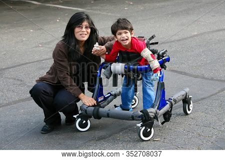 Asian Mother  Helping Little Disabled Son  Walk In His Walker Outdoors  On Sidewalk Or Pavement