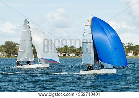 Two Sailing Dinghies Racing At A Childrens Yachting Regatta. Teamwork By Junior Sailors Racing On Sa