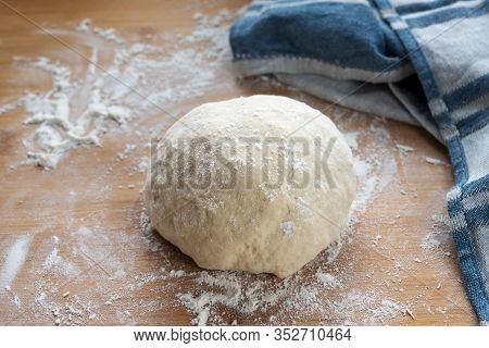 Raw Yeast Dough For Bread Or Cake Ready To Rise On A Wooden Baking Board Some Flour And A Blue Kitch