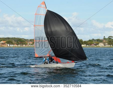 Kids Racing A Small Sailboat With A Black Spinnaker At A Junior Yachting Regatta. Teamwork By Junior