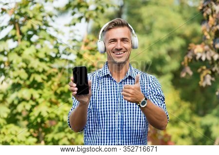 Best Phone To Play Music. Happy Man Give Thumbs Up To Phone. Handsome Guy Listen To Music Playing In