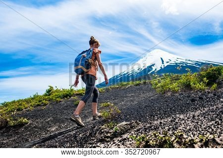 Young woman hiker walks on the loose rocky trail with snow capped volcano on the background. Trekking to volcano of Osorno in Chile
