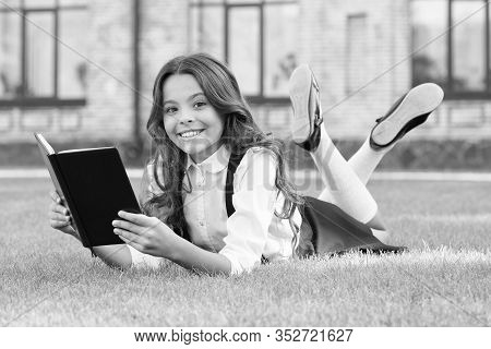 Your Dream Book. Happy Dreamer. Little Child Read To Dream. Small Girl Relax Reading Book On Green G