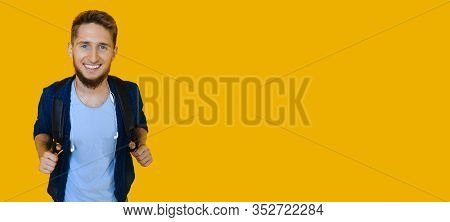 Ginger Caucasian Student Posing With A Bag On His Shoulders While Smiling Aside On A Yellow Wall Wit