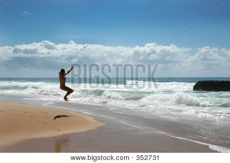 Man Jumping On Beach In Celebration Of Life