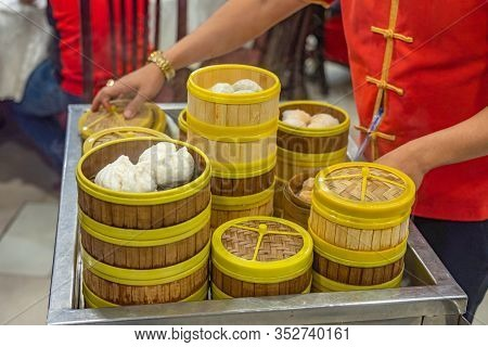 Waitress Serving Steamed Dimsum On The Cart In Chinese Restaurant