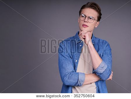 Pensive, Dreamy, Cute Sympathetic Young White Man In A Denim Shirt And Round Glasses, Holds His Hand
