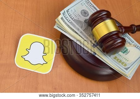 Snapchat Paper Logo Lies With Judge Gavel And Hundred Dollar Bills. Entertainment Lawsuit Concept