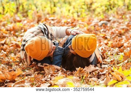 Lovely Couple Lies On The Ground In Autumn Leaves. Sensual Young Couple Walking In Autumn Park. Roma