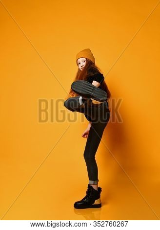 Smiling Frolic Red-haired Girl In Hat Black Tight Jeans And Brutal Boots Shoes Is Kicking Over Orang