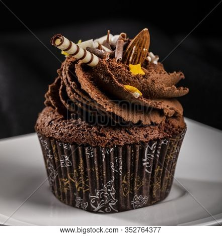 Close-up Of Brown Cupcake With Swirled Buttercream Icing And Decoration In Crimped Printing Wrapper