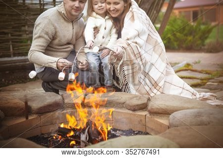 Cheerful Young Family With Little Daughter Toasting Marshmallow Over Bonfire While Enjoying Time Tog