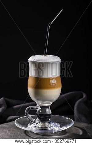 Multilayer Coffee With Frothed Milk And Drinking Straw In Transparent Glass Isolated On Black