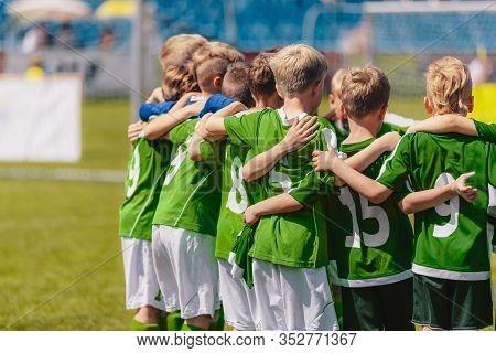 Kids Elementary School Sports Team In Green Jersey Shirts. Child Soccer Team Huddling. Junior Sports