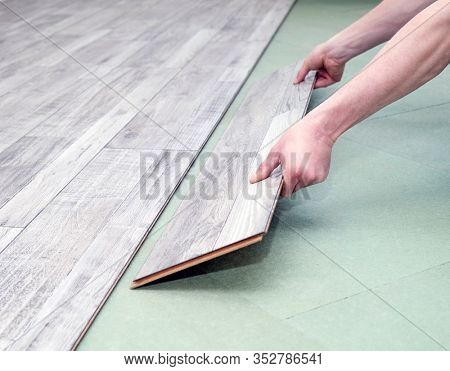 Close up of male hands installing new laminated flooring in room