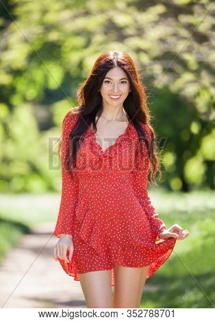 Young cute woman in red dress relaxing in the park. Beauty nature scene with colorful background, trees at summer season. Outdoor lifestyle. Happy smiling woman walking on green grass