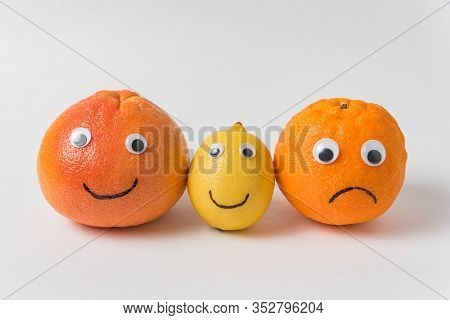 Grapefruit, Lemon And Orange With Funny Faces On White Background. Optimist And Pessimist Concept.