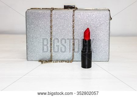 Glittery Silver Clutch Bag With Red Lipstick Isolated On White Background With Copy Space.