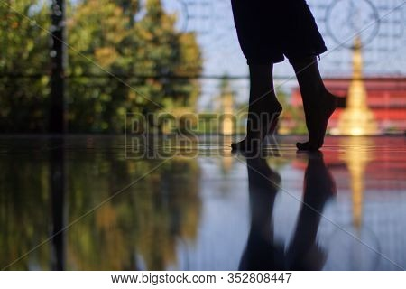 Silhouette Of Woman's Feet Walking On Tiptoe On Floor Of Buddhist Temple, Mirror Reflection Of Feet