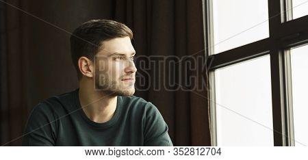 Millennial Guy Portrait. Confident Young Man Looking Aside Sitting Near Window In Modern Loft Interi