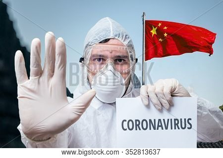 Doctor In Coveralls Warns Of Coronavirus Infection In China. Chinese Flag In Background.