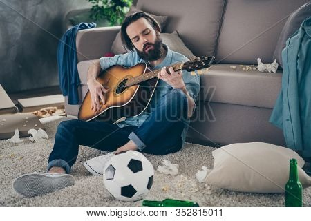 Photo Of Hipster Guy With Long Beard Sitting Carpet Near Sofa Holding Guitar Dont Mind Chaos After S