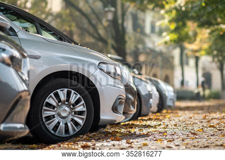 Modern Cars Parked On City Street Side In Residential Discrict. Shiny Vehicles Parked By The Curb. U