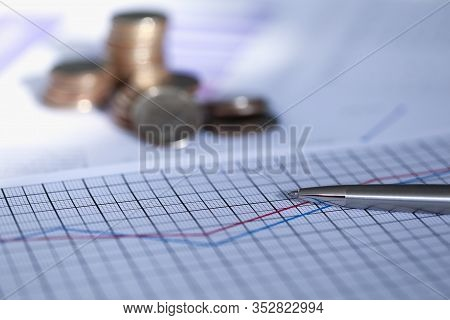 Silver Pen Lies On Report With Graph Next To Coin. Scaling Business Helps Capture Market And Dictate