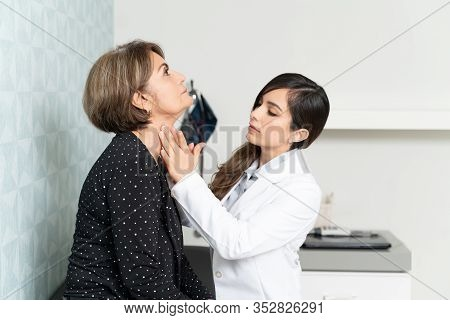 Senior Woman Visiting Female Geriatrician For Thyroid Checkup In Hospital