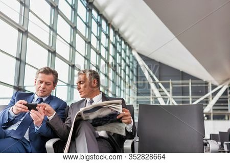 Mature businessman playing games on his phone while sitting and waiting for boarding in airport