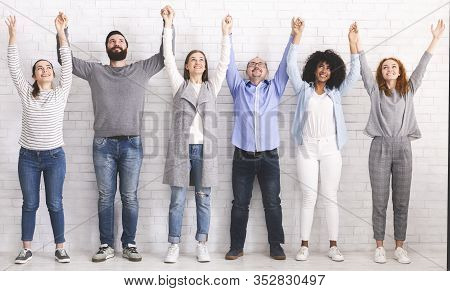 Teambuilding Concept. Group Portrait Of Happy People Holding And Raising Hands Together, Celebrating