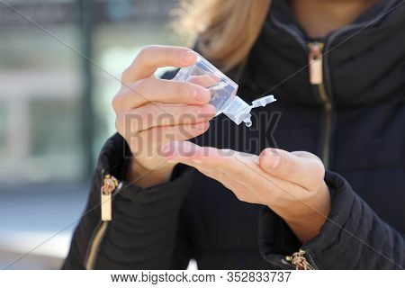 COVID-19 Pandemic Coronavirus woman hands using wash hand sanitizer gel dispenser, against Novel coronavirus (2019-nCoV) or Wuhan coronavirus in city street. Antiseptic, Hygiene and Healthcare concept.