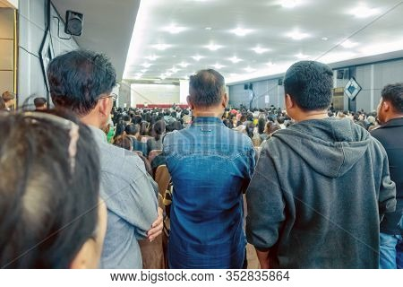 Backside View Of Spectators Standing In A Gathering In The Back Of Auditorium Full Of People. Select
