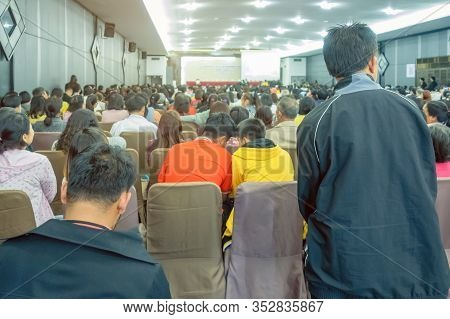 Backside View Of Spectators Sitting In A Gathering In The Back Of Auditorium Full Of People. Selecti