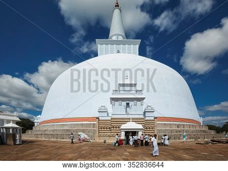 ANURADHAPURA, SRI LANKA - SEPTEMBER 26, 2009: ancient Ruwanweliseya Dagoba, Buddhist stupa with pilgrims built by king Dutugemunu in the 2nd cent. BC, third largest in the world, Golden Sand Stupa