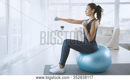 Strength Workout. Young Woman With Gym Ball And Dumbbells At Home, Blank Space