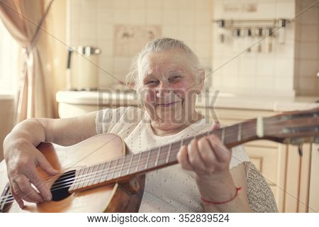 Mature Female Hobbies, 90 Year Old Grandmother Plays Guitar. Elderly Woman At Home.