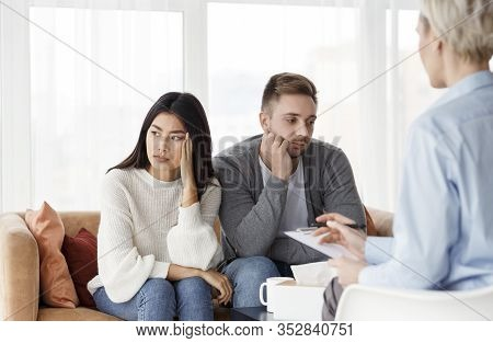 Couples Therapy. Diverse Spouses After Family Conflict Sitting In Psychologists Office. Selective Fo
