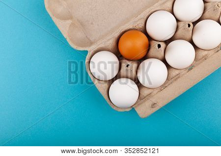 Egg Chicken Eggs. Top View Of An Open Gray Box With White Eggs Isolated On A Blue Background. One Eg